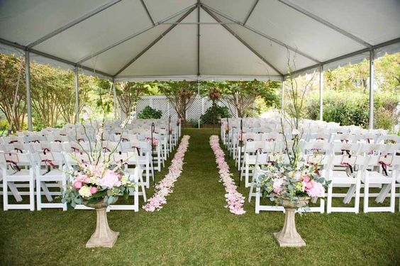 Tented wedding ceremony .. Love the aisle flowers! Needs draping.