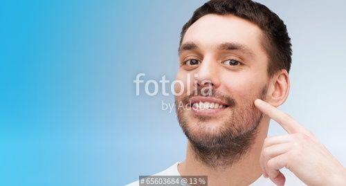 """""""smiling young handsome man pointing to cheek"""" Fotos de archivo e imágenes libres de derechos en Fotolia.com - Imagen 65603684"""
