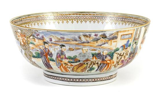 A Chinese Export 'Mandarine' famille rose enameled porcelain punch bowl- 18th century.  Depicting scenes of gentlemen and ladies at leisure reserved on a geometric ground; the interior rim lined in a gilt band of fleur de lys motifs. height 4 1/4in (10.5cm); diameter 10 1/4in (26cm)