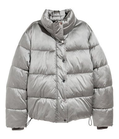 Silver-colored. Padded jacket with a high stand-up collar. Zip and wind flap at front with snap fasteners, side-seam pockets, and concealed drawstring at