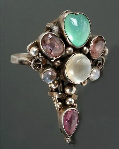 Dorrie Nossiter (attrib.). No details on the http://www.dorrienossiter.co.uk/where-to-buy/dreweatts.html page. Dreweatt Neate sold an Arts and Crafts gem set silver coloured ring, attributed to Dorrie Nossiter, unmarked, the tapering head with wire scrolls and beadpoints (no photo), 24 June 2008, £260: pretty sure it's this one. A heart-shaped stone at the top. Sold by Dreweatt Neate.