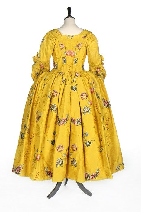 Rear view, robe à l'anglaise, England (Spitalfields), c. 1750. Yellow brocaded silk, woven with brightly coloured large-scale oriental poppies, posies and swags, the ground figured with arabesques and wine silk spotted cartouches, linen lining, trimmed with pinked furbelows; stomacher trimmed with rosettes and braid.
