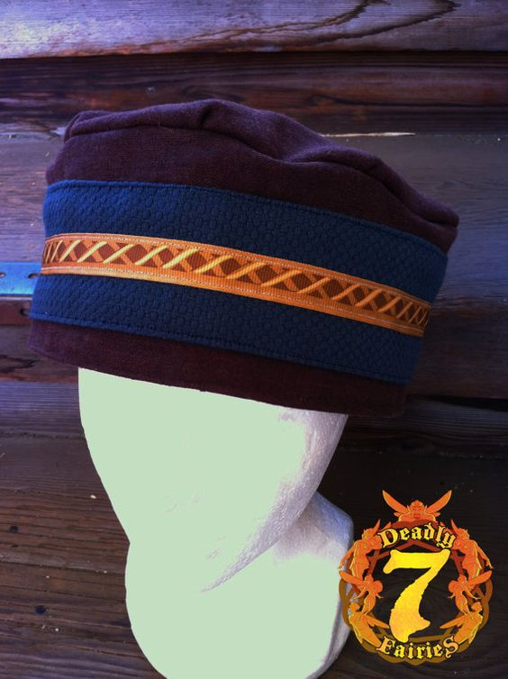 """This is what I call the """"gypsy"""" hat. This design I created when building a gypsy outfit. The hat is made from a Brown Linen. The brim has Navy Blue band, with a printed brown ribbon on top of that. It is fully lined and has denim as interfacing to make it more durable. It measures 24.5"""" on the inside."""