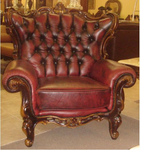 Victorian style red leather arm chair with wood trim.