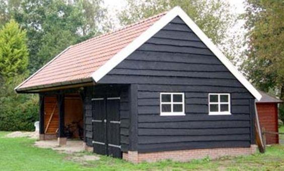 Deze donkere kapschuur met carport is voorzien van lariks hout en kruisroedes in de ramen.
