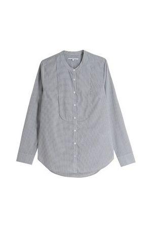Chemise en coton unie ou à fines rayures selon les modèles, aux manches longues et au col officier. Elle se pare d'un plastron discret, d'une patte de boutonnage centrale, de poignets cassés à 2 boutons et d'une base arrondie plus longue sur l'arrière que sur l'avant.