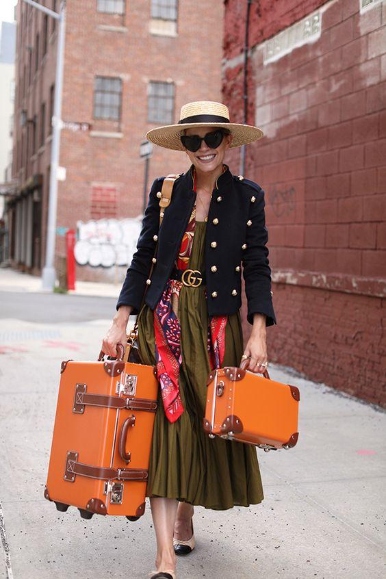 Chic Fall Travel Style | Cropped Women's Military Jacket, Silk Scarf, Olive Midi Dress, Oversized Straw Hat | Orange Streamline Luggage