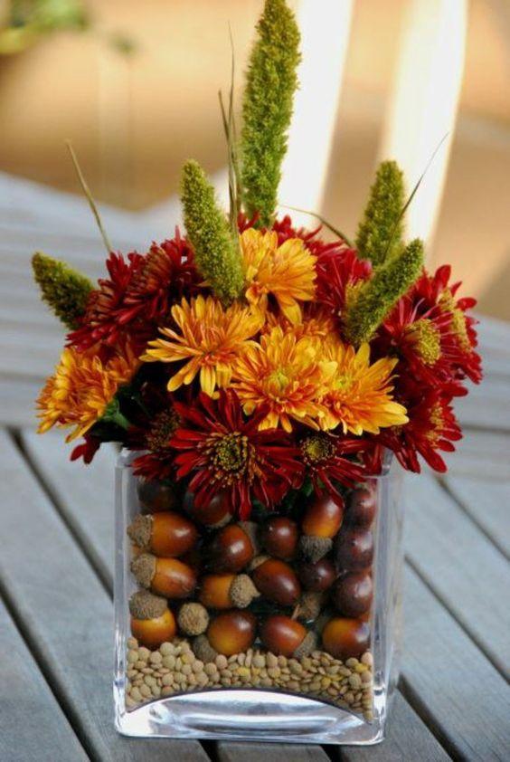 un verre transformé en vase décoratif avec des glands et fleurs