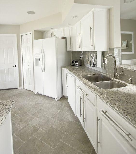 Kitchen with white appliances. Love the grey floor and the glass subway tile backsplash: