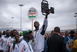 """Members of Niger""""s Olympic team pose for selfies prior to a welcoming ceremony at the athletes village of the Rio 2016 Olympic Games in Rio de Janeiro on August 3, 2016"""