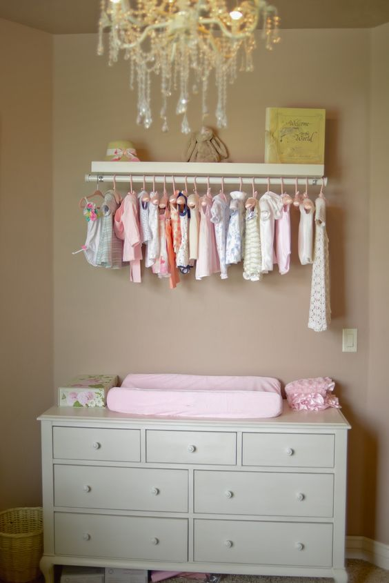 I love this idea - decorating with the tiny clothes in plain view. I'd replace with shelving once the clothes started getting too long.