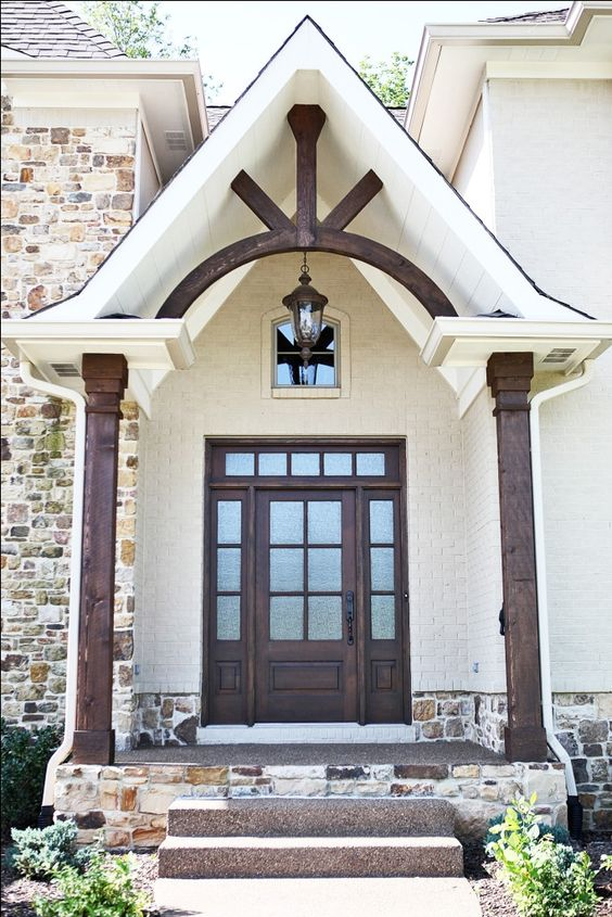 Matching stained wood beams, gable pediment, & front door lend a cohesive rustic element to this home.: