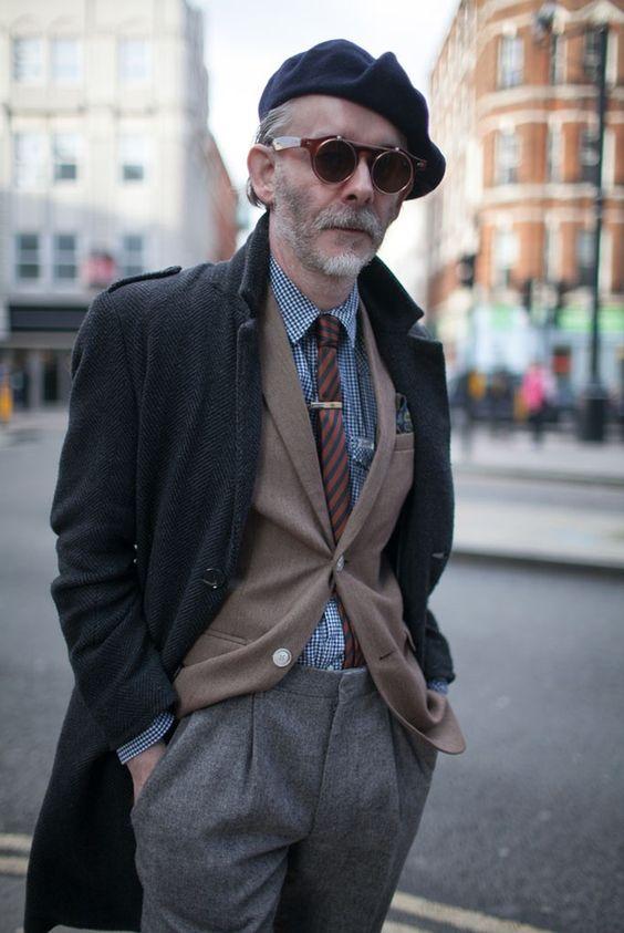 Street Style londonien pantalon gris veste Beige(Chinés), cravate rayée brun et camel chemise Vichy bleu et blanche , pardessus noir Chevrons, casquette et lunettes steampunk
