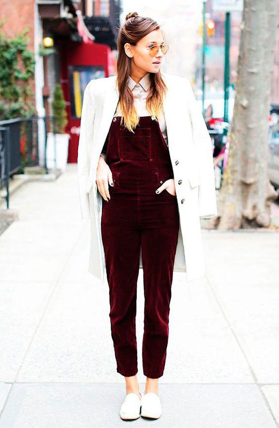 Street style look com macacão jardineira vermelho de veludo, camisa branca, sapato branco e sobretudo.: