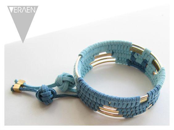 Massiver Armreif (hier in gold) mit zwei Farben Alcantaraband(hier in blau & türkis) in Mustern durchbrochen und goldenen Würfeln mit Schmuckknoten als Anhänger.