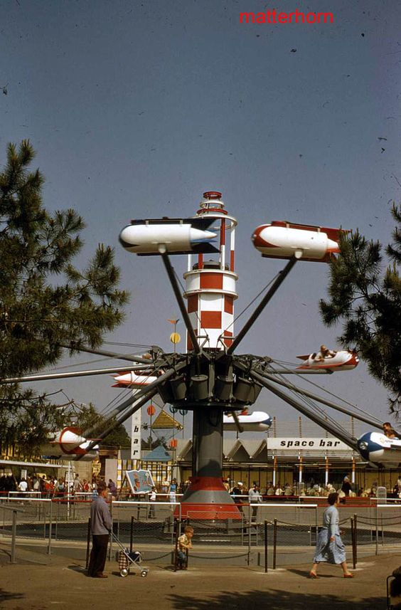 Disneyland guests take flight in the Astro Jets, which replaced Tomorrowland's Court of Flags. The Space Bar and a storybook sign advertising the Skyway are seen beyond, 1956.   stuff from the park