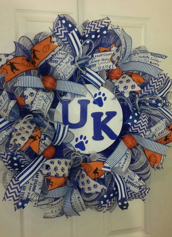 Kentucky Wildcat fans are everywhere so get your wreath now to decorate your door and make sure your neighbors know who you support. Sure to attract lots of attention as this wreath is done in royal blue metallic and white stripe deco mesh accented by royal blue and white mesh ruffles, blue & white Kentucky and paw print ribbon, blue and white chevron, polka dot ribbons, basketball ribbon along with a wooden plate in the center with a hand painted U, K and paw prints. All of this is topped…