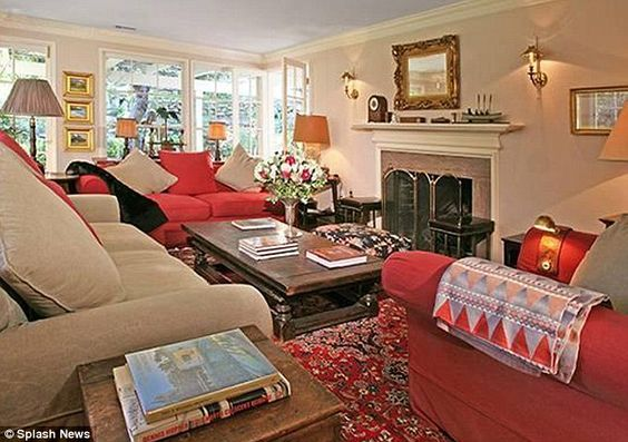 Cosy: Inside the white weatherboard home stands a cosy living room decorated in creams and warm reds