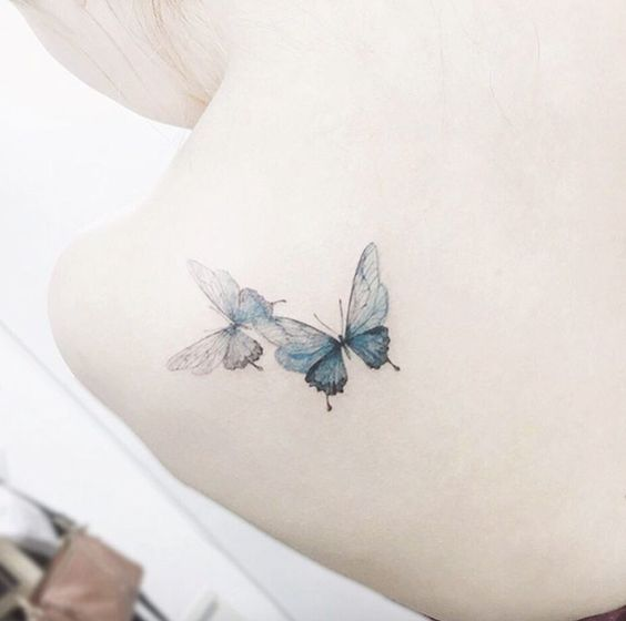 Playful butterfly tattoos on back shoulder by Tattooist Flower