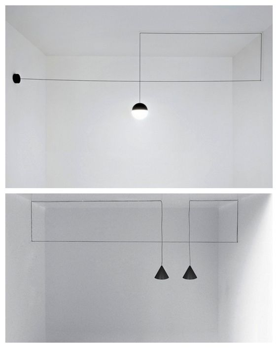 The lamps are hung with thin black electrical cords that draw bold geometric shapes in the air: