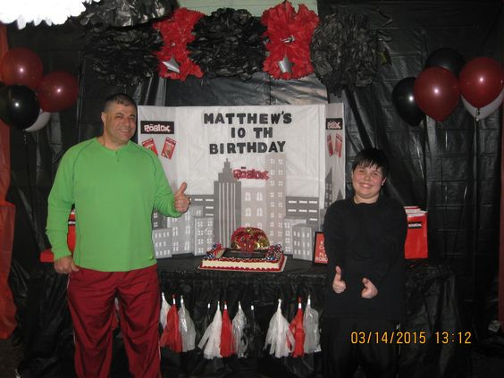 Roblox Birthday Party...My son and husband posing in front of the cake table.