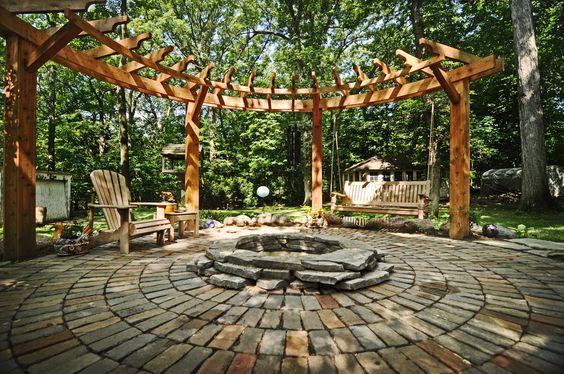 circular pergola, stone patio, and fire pit.