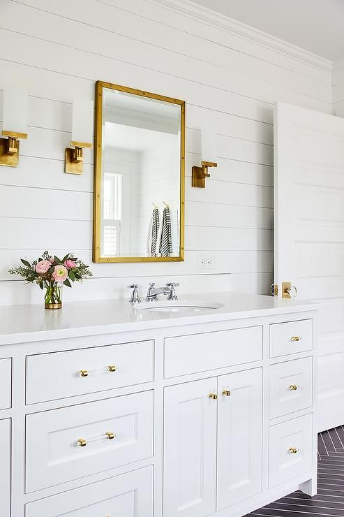 Stunning White Bathroom With Gold Accents Boasts A Restoration Hardware Rivet Mirror Hung From A White Shiplap Wa Shiplap Bathroom White Bathroom Gold Bathroom