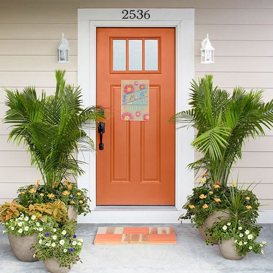 As if the door mounted flag (#756386) weren't welcoming enough against the sunny color selected for this front door (Emberglow, #HGSW1104), a pair of majesty palms wave their greeting in the breeze. More subtle color comes from the crossandra, coleus, and calibrachoa planted beneath the palms, with coleus, petunia, and dracaena in the smaller pots. A DIY parquet welcome mat can be painted the color of your choice (Clever Mantis, #HGSW2224, and Untamed Yellow, #HGSW1174, shown). #lowes #DIY
