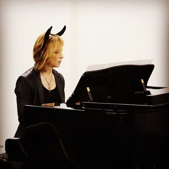 デビル風の角を頭につけてピアノを弾いているXJAPAN・YOSHIKIの画像