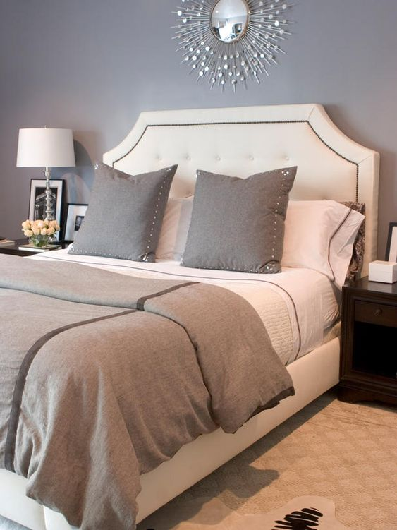 Glamorous Gray. A neutral, tufted and nail-studded headboard stands out against gray walls and bedding. Accessories are kept to a minimum, allowing the bed to take center stage. Love it!