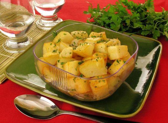 Foto com a receita de batata na manteiga na travessa, bem temperada com salsa. A receita está em uma travessa de vidro transparente, acompanhada de uma colher. Ao fundo está um ramo de salsa.