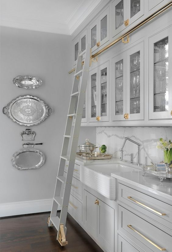 Grey butler's pantry with #brasshardware and sliding library ladder. Silver trays displayed on wall, marble slab backsplash, and glassfront cabinetry | Mitchell Wall Architecture & Design #brasshardware #libraryladder #greykitchen