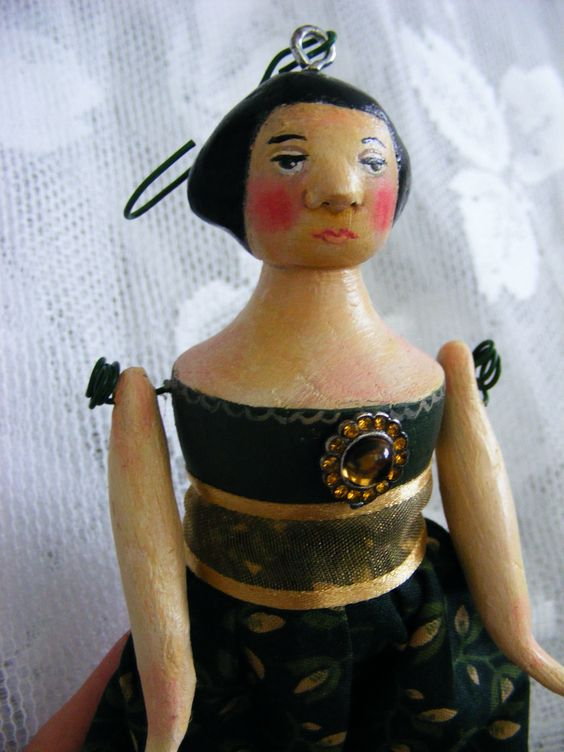 Miniature folk art doll ornament.