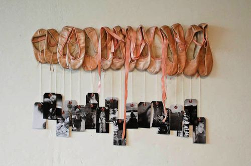 Ballet shoes with a picture hanging for every year of dance.