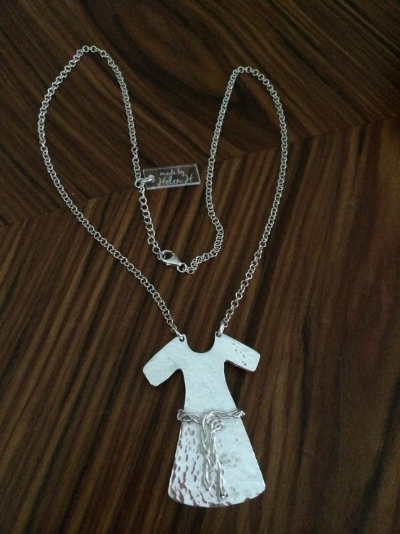 """A sterling silver neckless - a """"dress"""" with hammered surface and a """"belt"""" made of silverthread."""