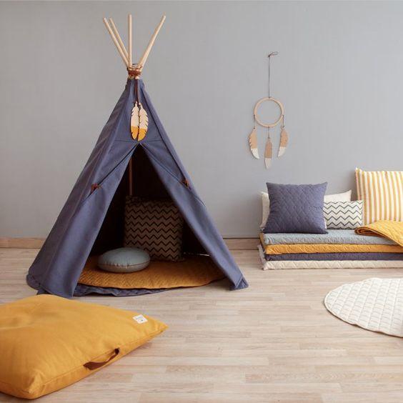 Un tipi pour la chambre d'enfant. Place à l'imagination dans la chambre d'enfant avec ce tipi qui conjugue tendance graphique et tendance navajo. Cette cabane atypique s'accompagne de jolis coussins graphiques, de plumes et d'attrape-rêves, la parfaite panoplie pour jouer au petit indien en herbe !: