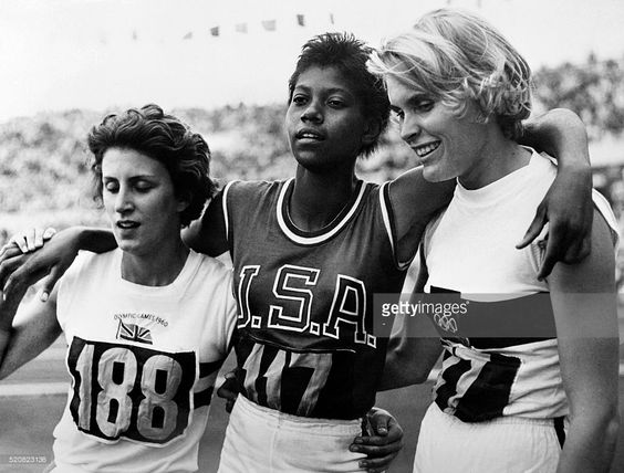 Nicknamed 'the black gazelle', U.S champion Wilma Rudolph (C), who have just won the Olympic 200m event, pose between German Jutta Heine (R), who finished 2nd and British Dorothy Hyman, who finished 3rd, 06 September 1960 in Rome where she captured three gold medals: 100m, 200m and 4x100m. Wilma Rudolph has been the first ever woman to run the 200m event in less than 23 seconds. / AFP / EPU / -