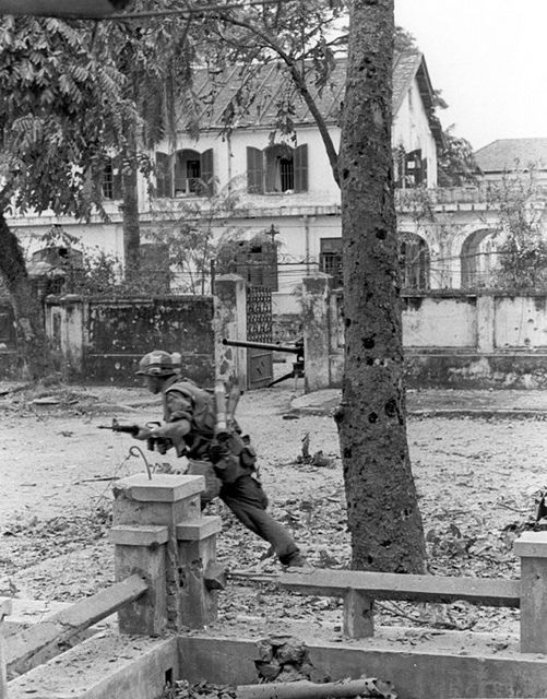 Under Fire -- A Leatherneck moves out under intense enemy .50 caliber machine gun fire during heavy street fighting taking place in the old Imperial Capital of Hue. Brigadier General Edwin H. Simmons Collection ~ Vietnam War
