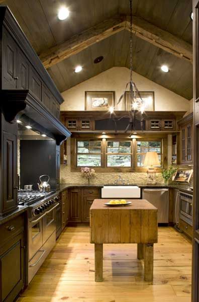 A vaulted ceiling covered in wooden planks and crossed by rough-hewn beams gives this kitchen the feeling of an old country farmhouse.