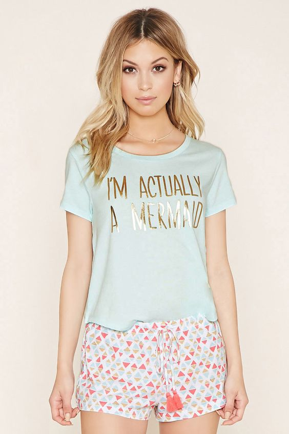 """A knit PJ set complete with a short-sleeved tee featuring a metallic """"I'm Actually A Mermaid"""" front graphic and a curved hem, along with a pair of shorts featuring an allover geo print with a glittery finish and a tasseled drawstring at its elasticized waist."""