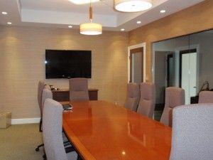 Grass cloth wallpaper helps warm up this office space. Recessed lighted soffit. Custom shaped conference table.