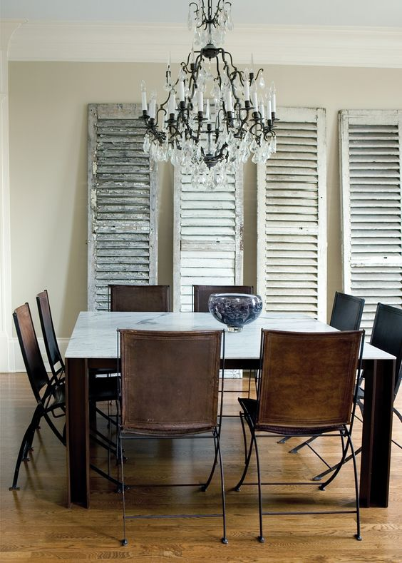 Leather folding chairs and old shutters in dining room by Susan Sing