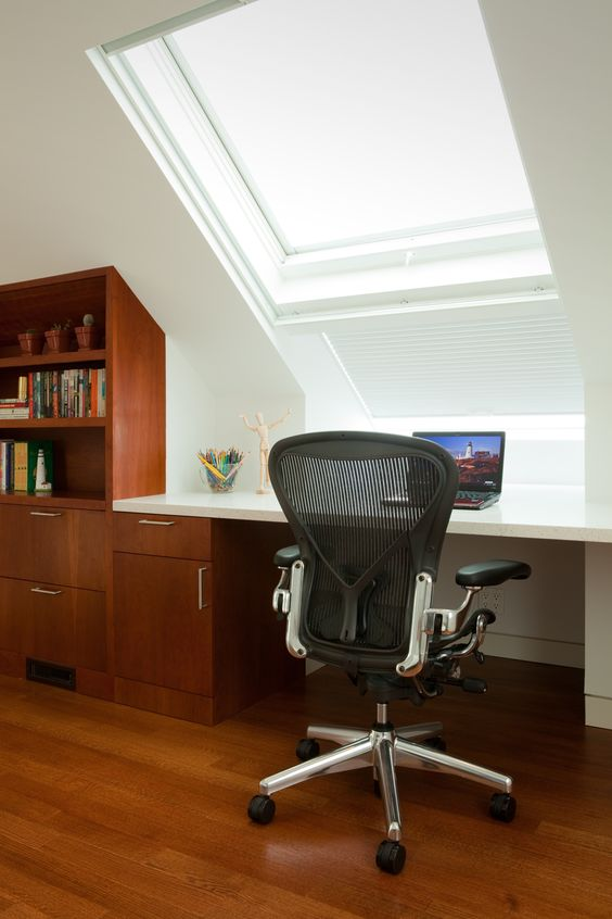 The upper bedroom is used as an office as well with built-in cabinetry forming a computer desk facing a large double skylight that is a window out to the view. Photo Credit: John Sutton Photography