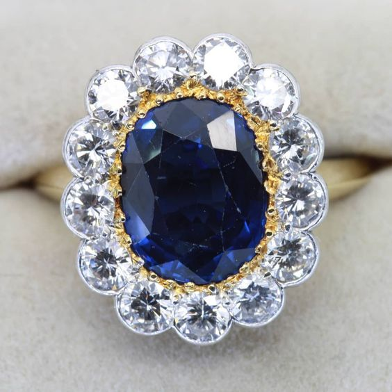Beautiful deep blue sapphire with diamond surround on yellow gold