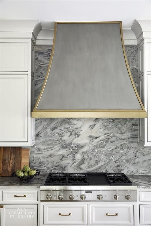 Silver And Gold French Range Hood Takes Notice Between Gray Cabinets Above A Gray Marble Slab Cooktop Backsplash Range Hood Grey Marble Kitchen Kitchen Marble