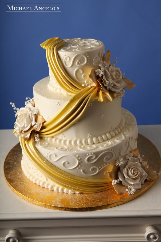 Golden Drapes #15Drapery  This buttercream three tier cake is decorated with swirls and swiss dots. Each layer is drapped with a golden lustered fondant drape then accented with a large jumbo rose spray.