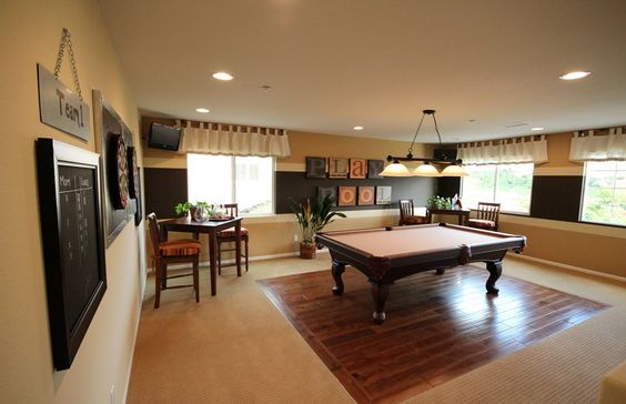 Pool table in middle of the room with small tables in corners. Darts on the wall.