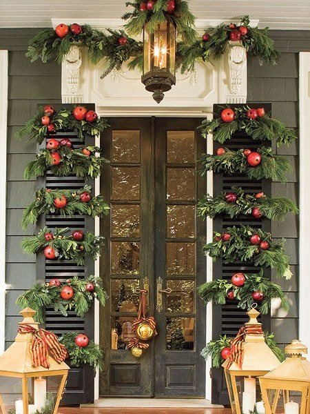 Beautiful front porch decorated for Christmas with large lanterns, greenery, and pomegranates