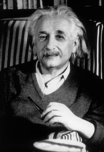 微笑んで椅子に座っているアルベルト・アインシュタインの壁紙・画像