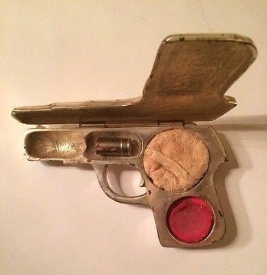 Earlier than the roaring 20s, but just as saucy as if a flapper carried it. Powder, rouge, lipstick in a pistol-shaped compact.